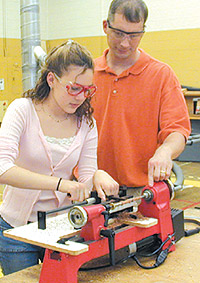 Sheldon poremba woodworking teacher instructs kelsey farver on how